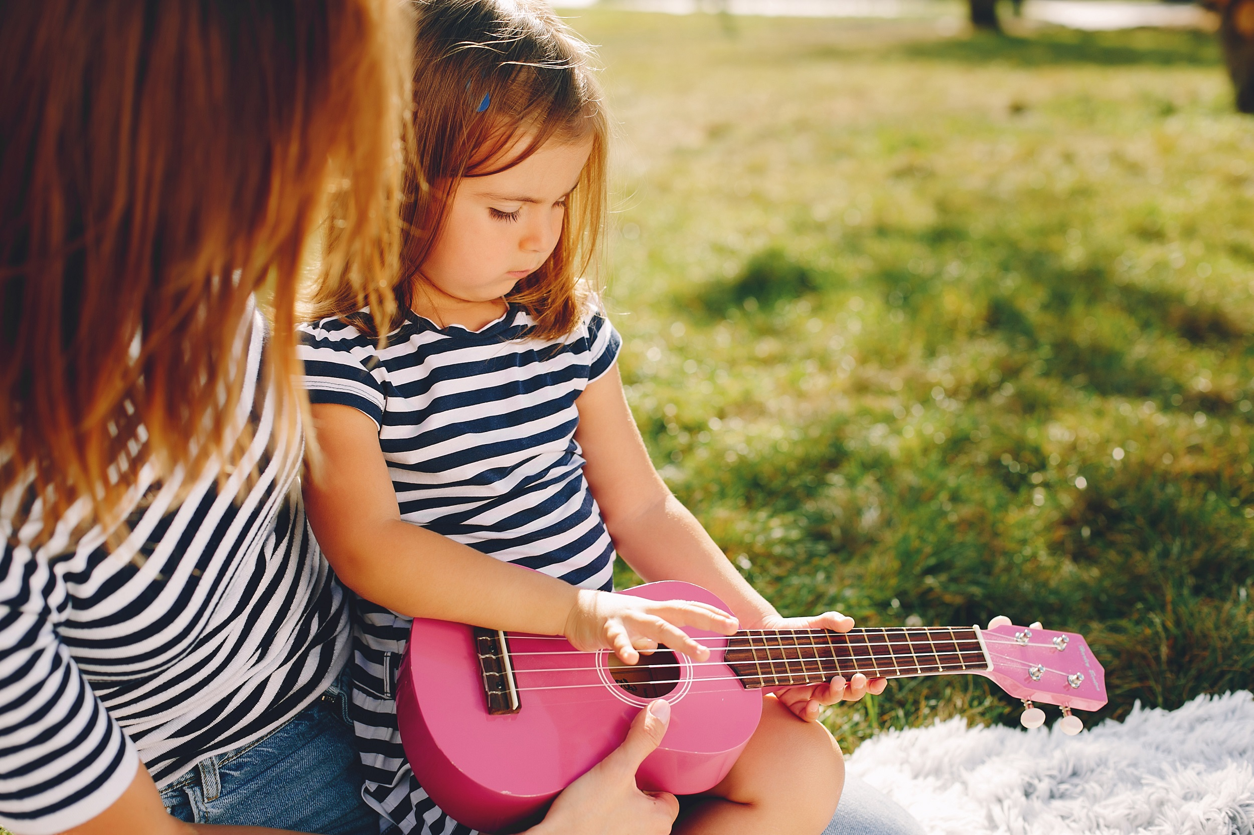 Family sitting in a summer park. Mother in a white t-shirt. Cute little girl with a pink guitar
